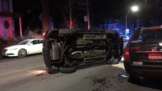 Driver hits parked car, flips on its side in Boston